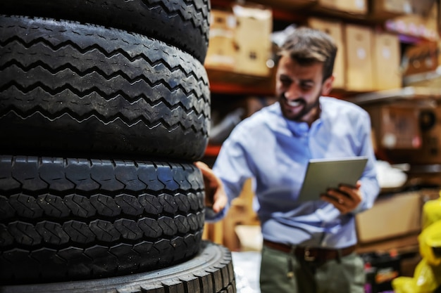 Bearded smiling supervisor standing in storage of shipping firm, holding tablet and checking on tires. selective focus on tires.