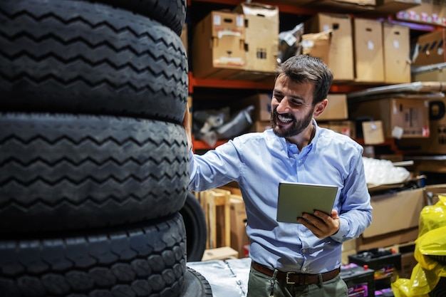 Bearded smiling supervisor standing in storage of shipping firm, holding tablet and checking on tires.