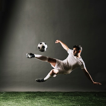 Bearded soccer player falling and kicking ball