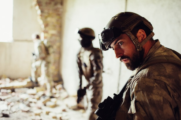 Bearded soldier is standing with his comrades in a ruined room.