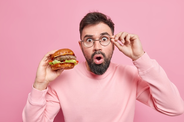 Bearded speechless man staress surprised keeps hand on rim of glasses finds out shocking news about how harmful fast food is holds appetizing hamburger wears casual jumper
