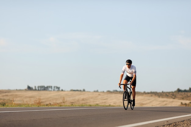 시골 사이에서 자전거를 타는 흰색 티셔츠와 검은 색 반바지에 수염을 기른 스포츠맨