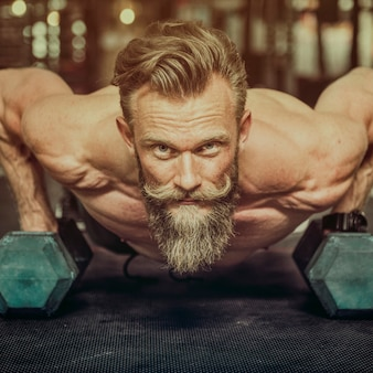 Bearded strong man weightlifting at the gym