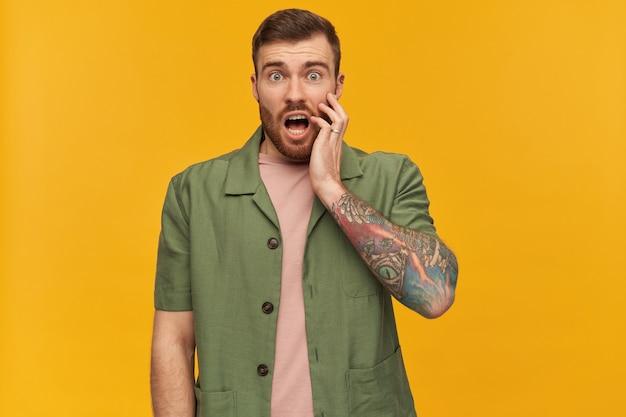 수염 난 기절 남자, 갈색 머리를 가진 불만 남자. 녹색 반팔 재킷을 입고. 문신이 있습니다. 충격에 얼굴을 만졌다. 노란색 벽 위에 절연