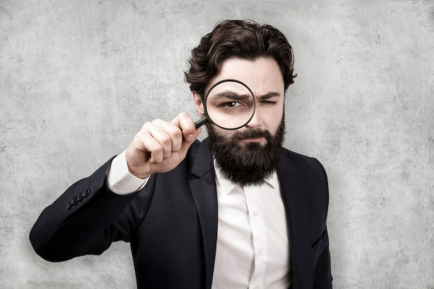 Bearded stylish businessman with magnifier on concrete wall wall, search concept