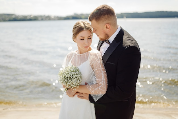 A bearded, stylish groom in a suit and a beautiful blonde bride in a white dress with a bouquet in her hands are standing and hugging in nature in the pine forest.