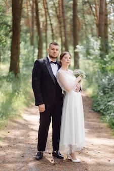 Uno sposo barbuto ed elegante in abito e una bella sposa bionda in abito bianco con un bouquet in mano sono in piedi e si abbracciano nella natura nella foresta di pini.