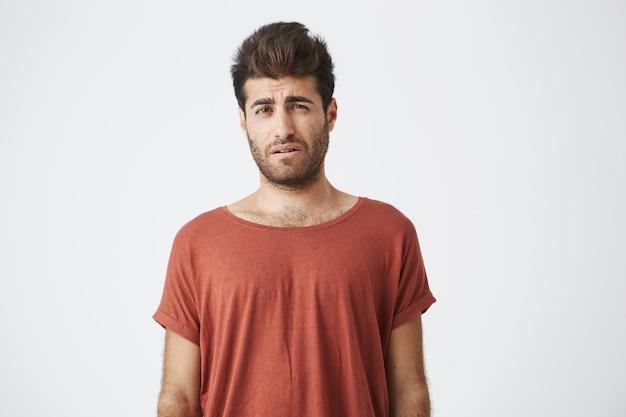 Бородатый стильный мужчина недоволен взглядом стоя в повседневной ткани против белой стене. у молодого человека возникли проблемы с недовольством и недовольством