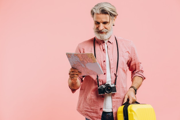 Bearded stylish man holds a yellow suitcase and chooses a country to travel on map.