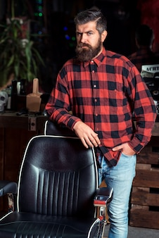 Bearded stylish man. stylish man at barber shop. trendy barber shop. stylish man with beard in plaid shirt standing near vintage barber chair.