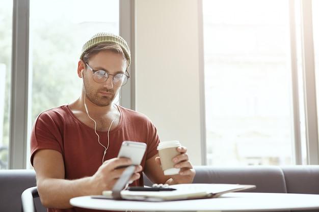 ひげを生やしたスタイリッシュな男が赤いカジュアルなtシャツと眼鏡を着用し、一般的な携帯電話を保持しています。