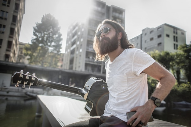 Bearded stylish man with a guitar