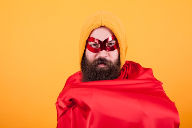 Bearded superhero with red mask showing his red cape over yellow background. handsome superhero.