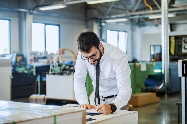Бородатый руководитель с очками и в рубашке и галстуке проверяет качество отпечатанных листов, стоя в типографии.
