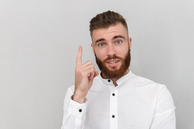 수염을 기른 놀란 남자가 손가락을 위쪽으로 가리키고 회색 벽 위에 고립된 앞을 바라보고 있다