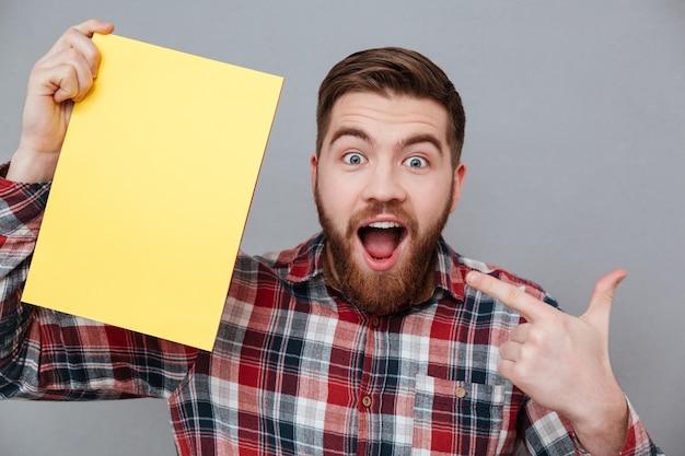 Bearded surprised man in shirt holding blank board