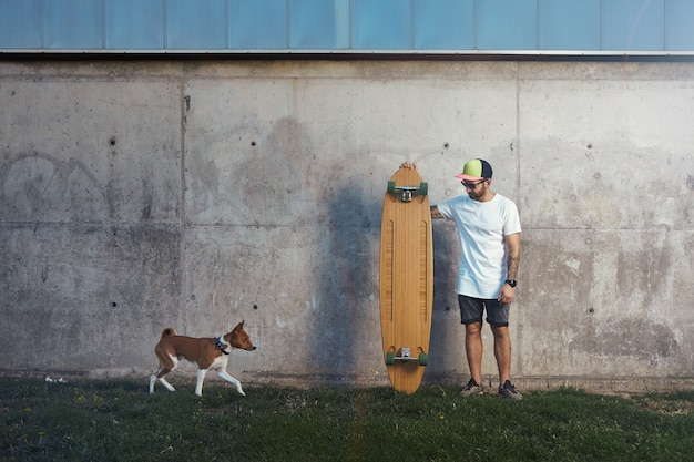 Bearded and tattooed longboarder standing next to a concrete wall looking at an approaching brown and white basenji dog