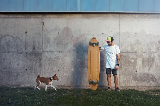 Longboarder barbuto e tatuato in piedi accanto a un muro di cemento guardando un cane basenji marrone e bianco in avvicinamento
