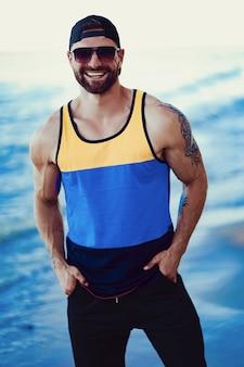 Бородатый татуированный мужчина на курорте в спортивной рубашке, кепке и солнцезащитных очках на море