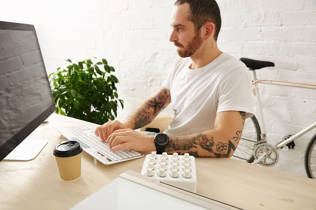 Bearded tattooed man in blank white t-shirt works on his computer at home, side view, summer time