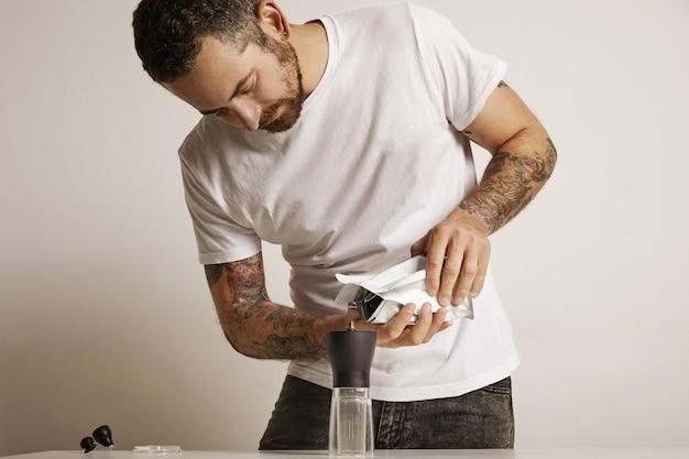 Uomo barbuto e tatuato che versa fondi di caffè in un moderno macinacaffè manuale da un sacchetto sventato bianco