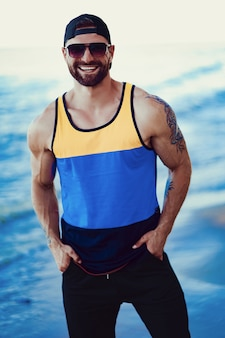 Bearded tattooed man at the resort in a sportive shirt, cap and sunglasses on the sea