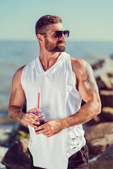 Бородатый татуированный манат на курорте в белой рубашке и в темных очках, сидя на скале, попейте коктейль на морской стене