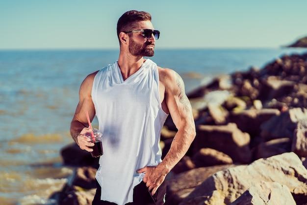 Бородатый татуированный манат на курорте в белой рубашке и в темных очках, сидя на скале, попивая коктейль на море