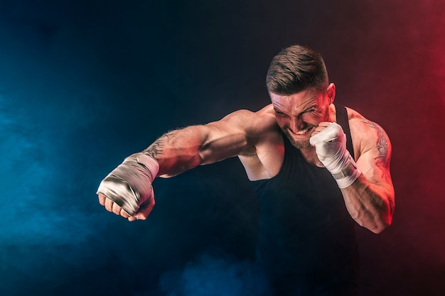 Bearded tattooed portsman muay thai boxer in black undershirt and boxing gloves fighting on dark background with smoke. sport concept.