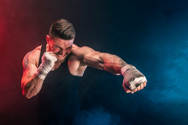 Bearded tattooed portsman muay thai boxer in black undershirt and boxing gloves fighting on dark wall with smoke. sport concept.