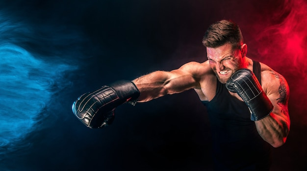 Bearded tattooed sportsman muay thai boxer in black undershirt and boxing gloves fighting on dark background with smoke. sport concept.