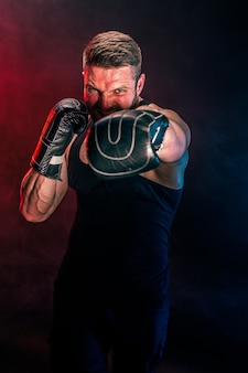 Bearded tattooed sportsman muay thai boxer in black undershirt and boxing gloves fighting on dark wall with smoke. sport concept.