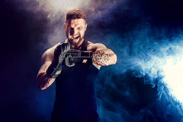 Bearded tattooed sportsman muay thai boxer in black undershirt and boxing gloves screams, motivates on dark wall with smoke. sport concept.