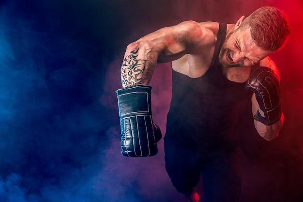 Бородатый татуированный спортсмен муай-тай боксер в черной майке и боксерских перчатках борется на темном фоне с дымом. концепция спорта.
