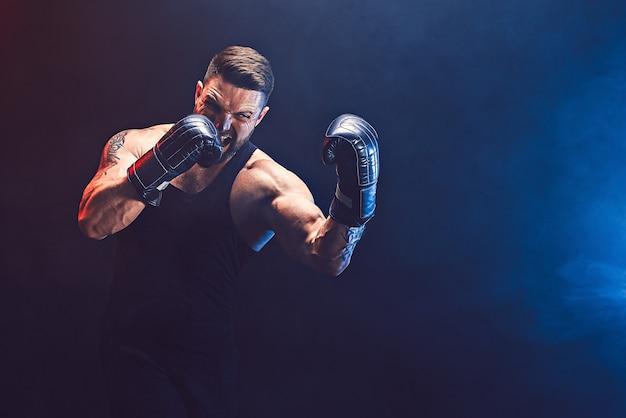 Бородатый татуированный спортсмен боксер тайского бокса в черной майке и боксерских перчатках борется на темной стене с дымом. концепция спорта.