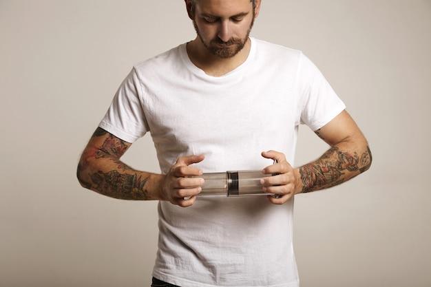 Giovane barbuto e tatuato in maglietta di cotone bianca vuota che tiene un aeropress chiaro grigio chiaro vuoto