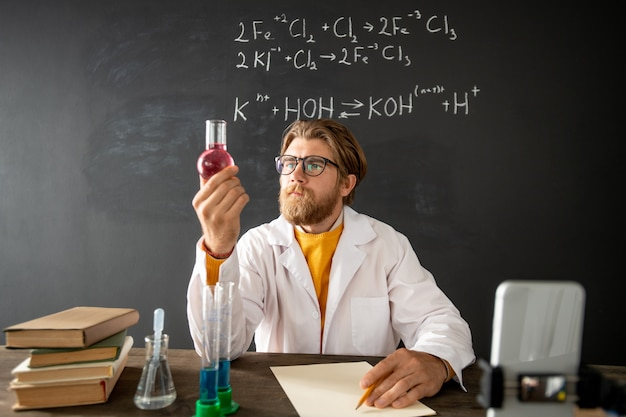 Bearded teacher of chemistry looking at tube with pink liquid substance while sitting by table in front of smartphone camera at lesson