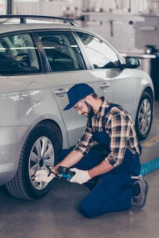 Bearded technician expert in blue overall checkered shirt analyzing tire