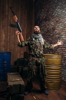 Bearded terrorist holding the kalashnikov rifle up. terrorism and terror, soldier in khaki camouflage