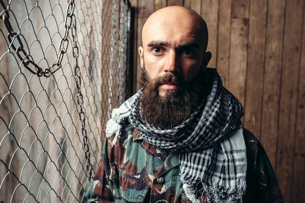金属グリッドに対して制服を着たひげを生やしたテロリスト