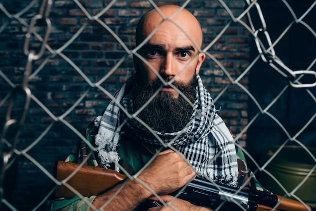 금속 격자에 대한 제복을 입은 수염 난 테러리스트