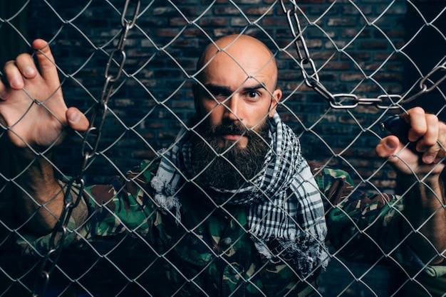 Bearded terrorist in uniform against metal grid