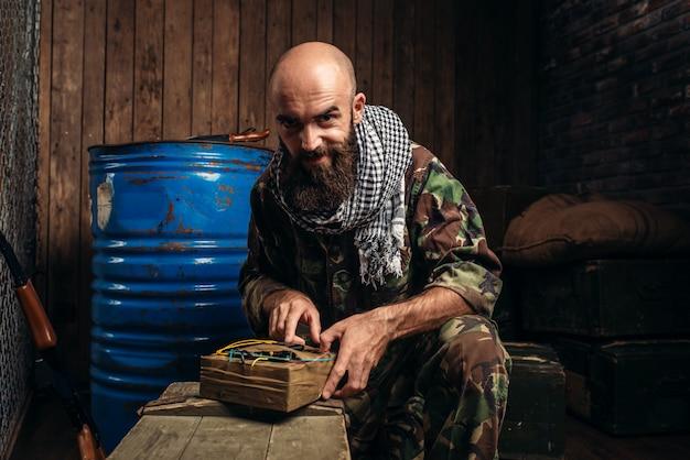 Bearded terrorist in uniform cocking a bomb