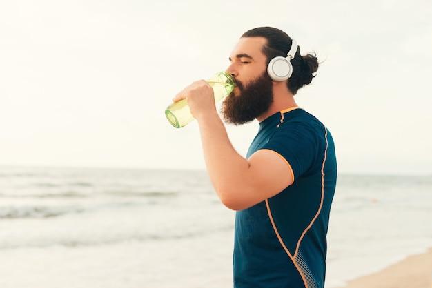 Bearded thirsty man wearing sportswear is drinking from his water bottle.
