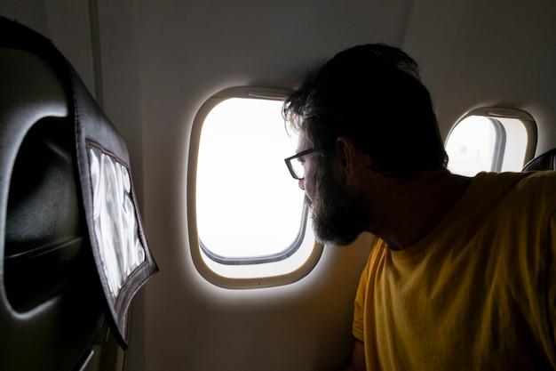 ひげを生やした旅行者の男が飛んで旅行している飛行機の中の窓の外を見る