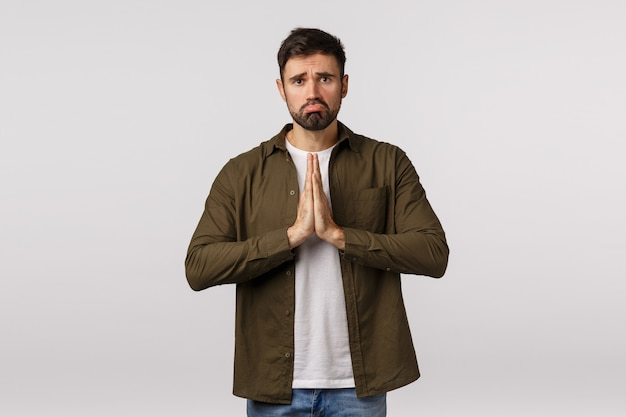Bearded unhappy guy in brown coat supplicating