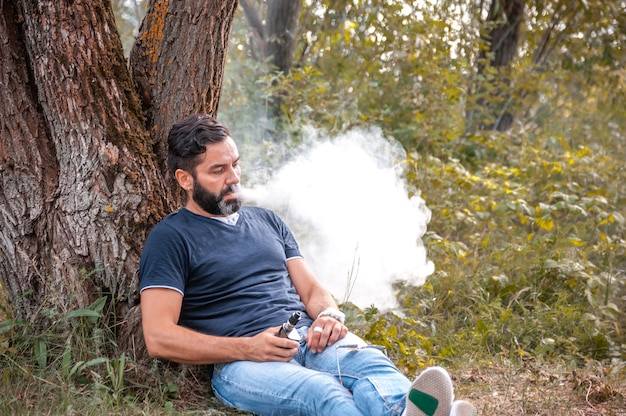 ひげを生やしたアーク男は電子タバコを吸う煙を吐き出す