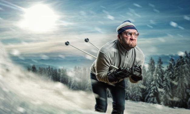 雪が降っている間速くスキーをする眼鏡のひげを生やしたヴィンテージスキーヤー