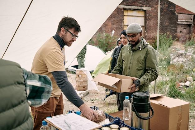 フードテントに立って難民に食べ物を与える黄色のtシャツを着たひげを生やしたボランティア