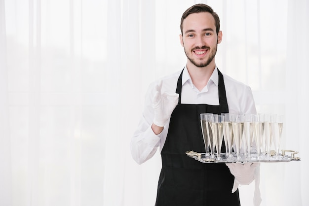 Bearded waiter holding metal tray